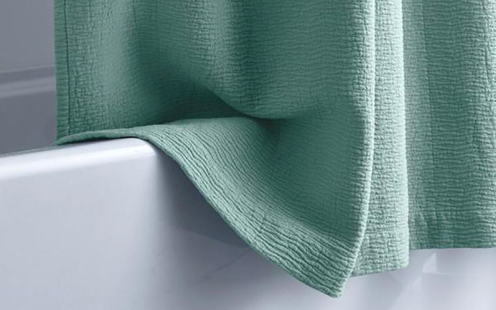 a thick green textured shower curtain hanging over bathtub
