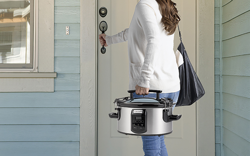 A woman carrying a slow cooker.