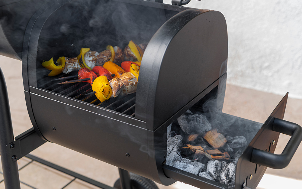 A charcoal smoker cooks skewers.