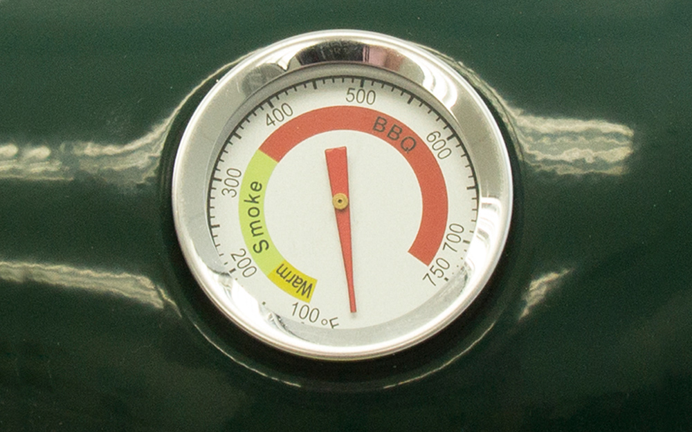 A dial measures the heat inside a smoker.