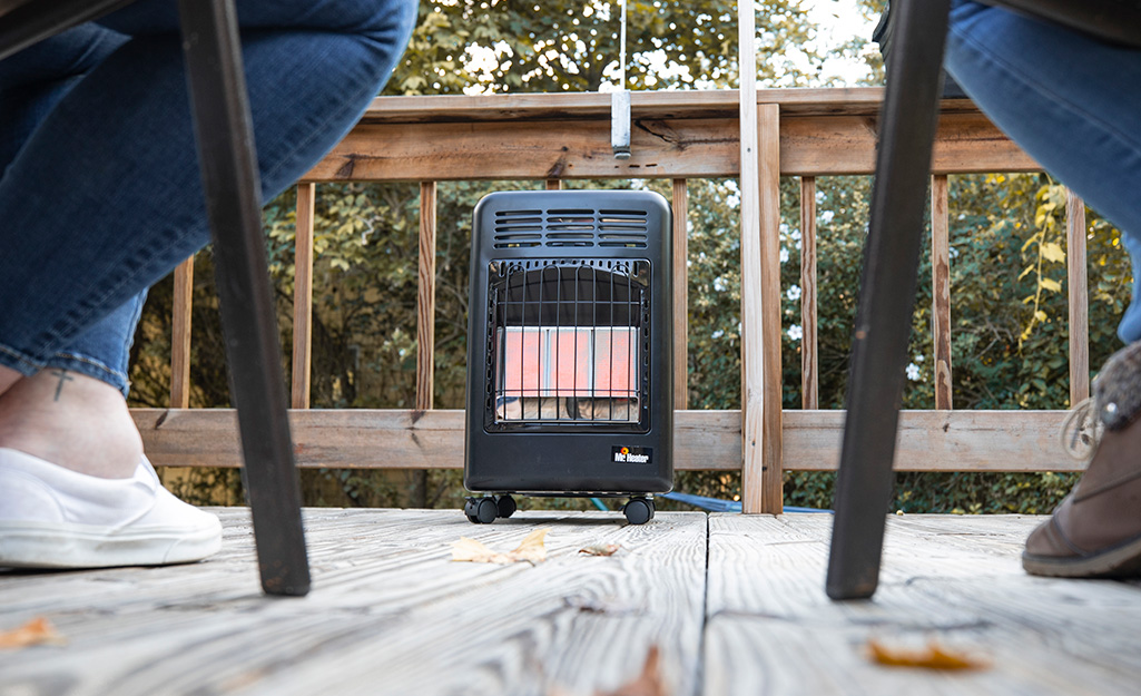 A propane heater is outside on a deck.