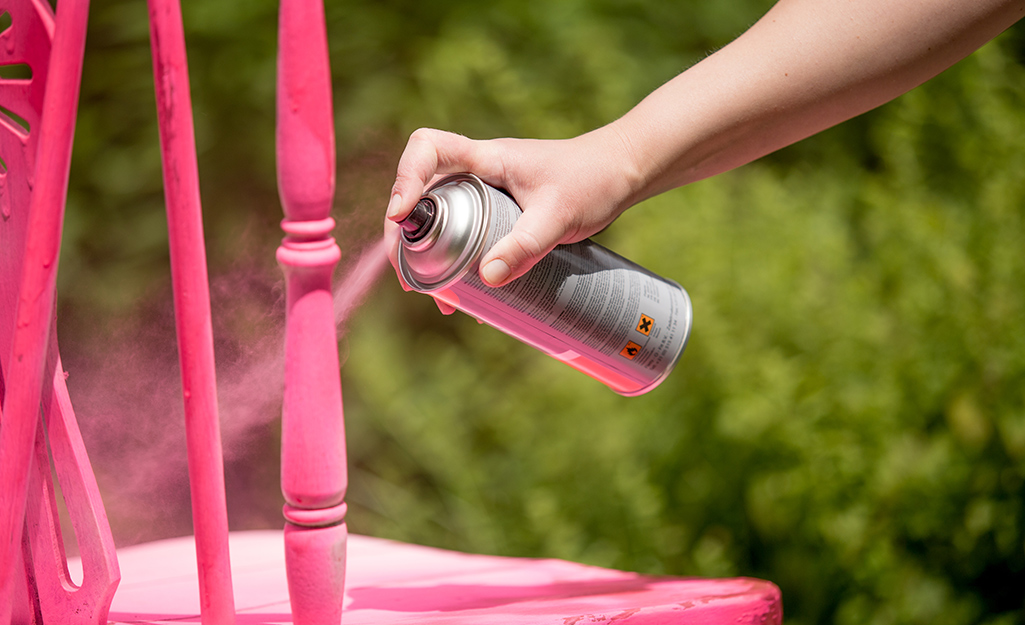 A person spray paints a wood chair bright pink.