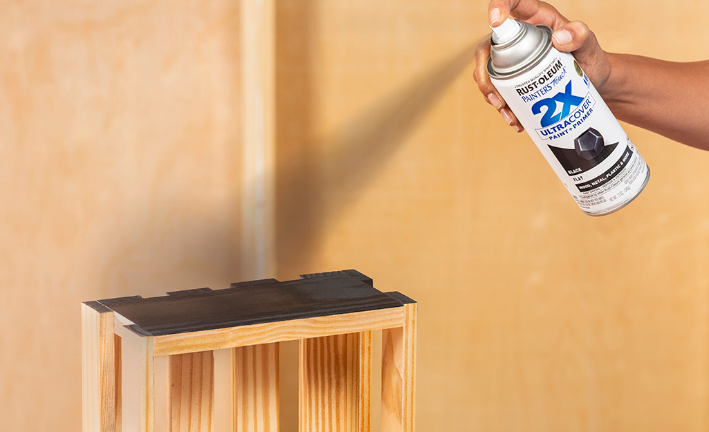 A person spray paints a wooden crate black.