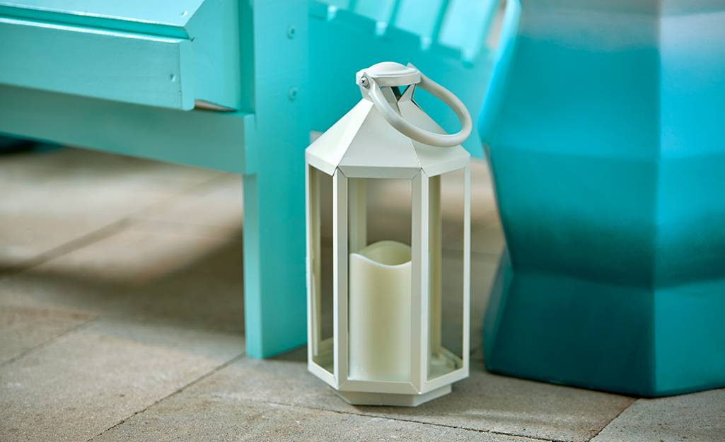 A white metal lantern sits on the ground beside two bright turquoise items.