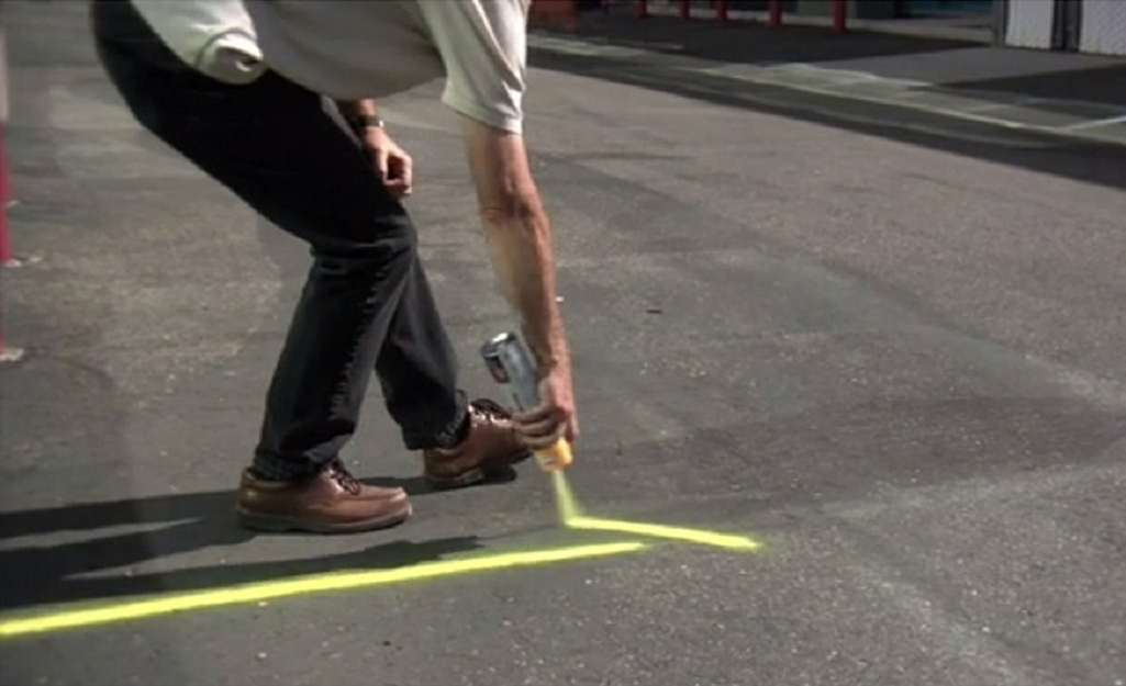 A person uses bright yellow spray paint to mark the pavement with lines.