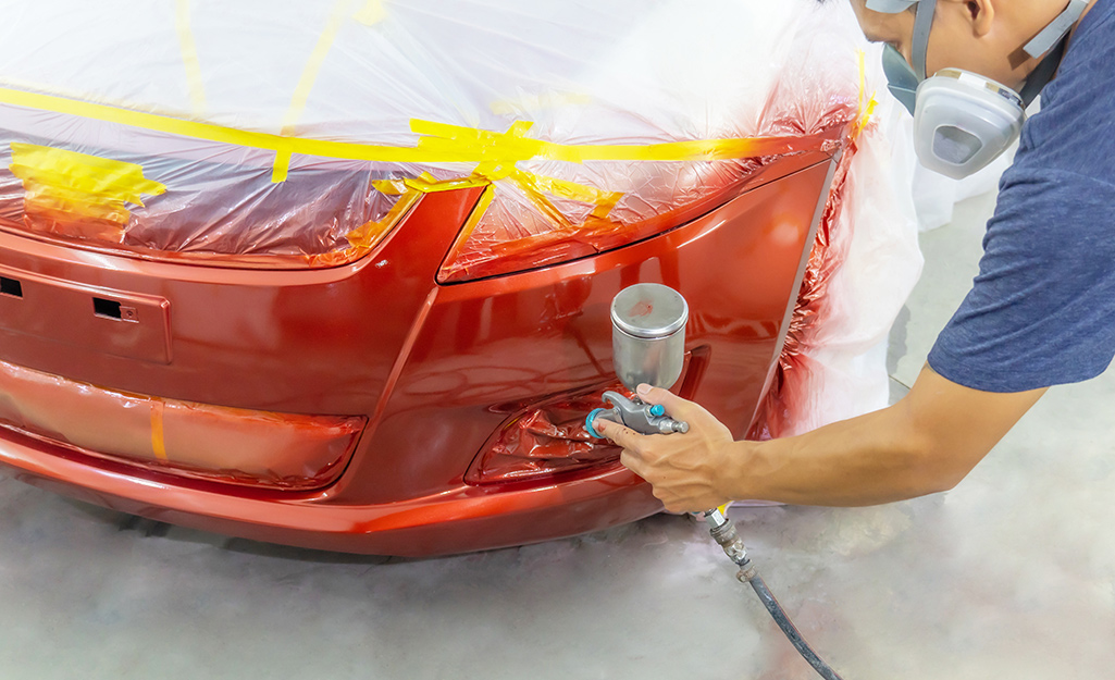 A person sprays a car with red paint.