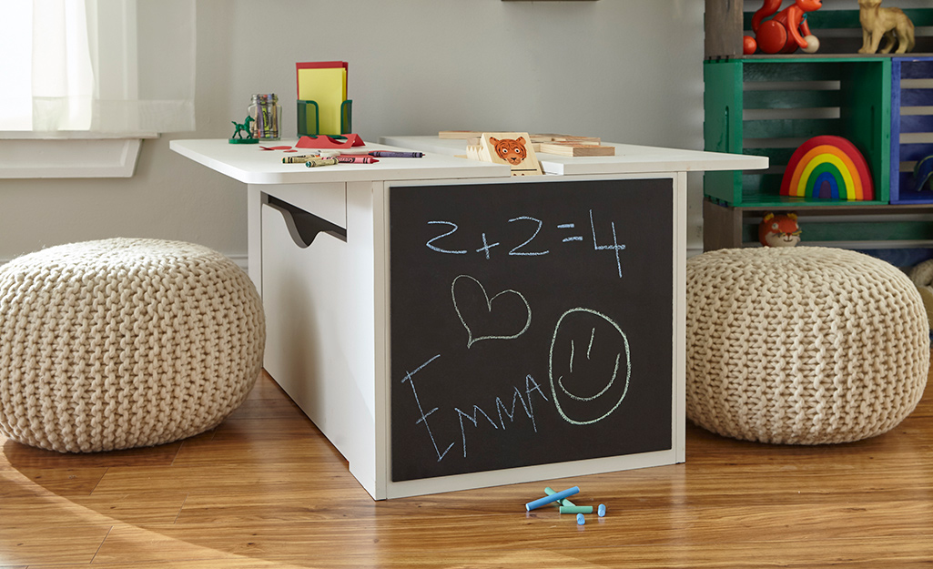 Chalkboard paint decorates one side of a child's table in a playroom.