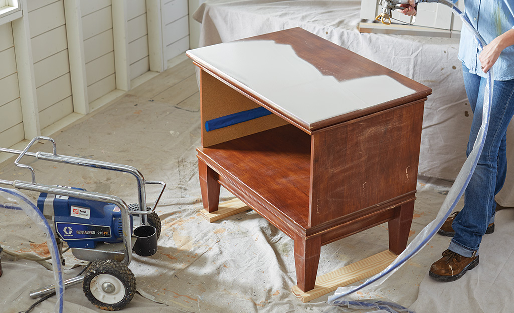 Drop cloths cover an indoor work space as a person sprays white paint onto a piece of wood furniture.