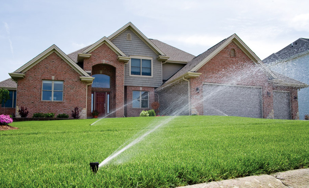 Sprinkler watering a front lawn.