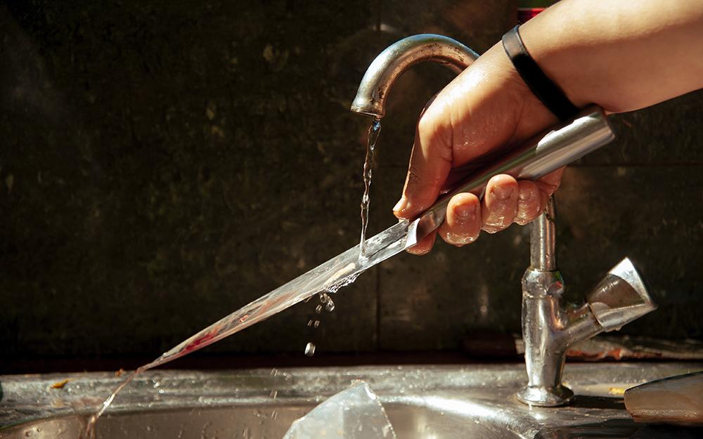 người rửa dao bít tết bằng thép không gỉ trong bồn rửa