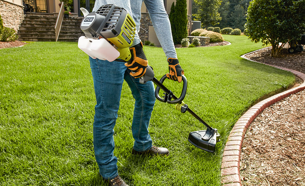 A person uses a gas string trimmer to edge flower beds.