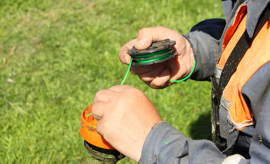 A person refills a string trimmer with fresh trimmer line.