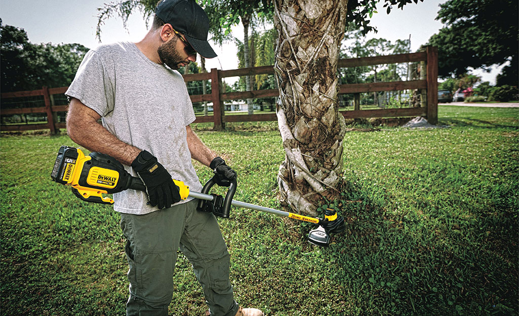 A man wearing safety glasses and work gloves operates an electric string trimmer.
