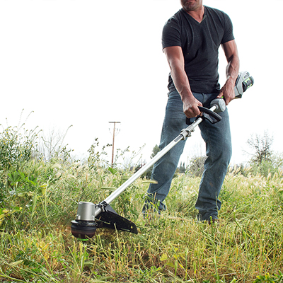 A man cuts back tall grass with a string trimmer.