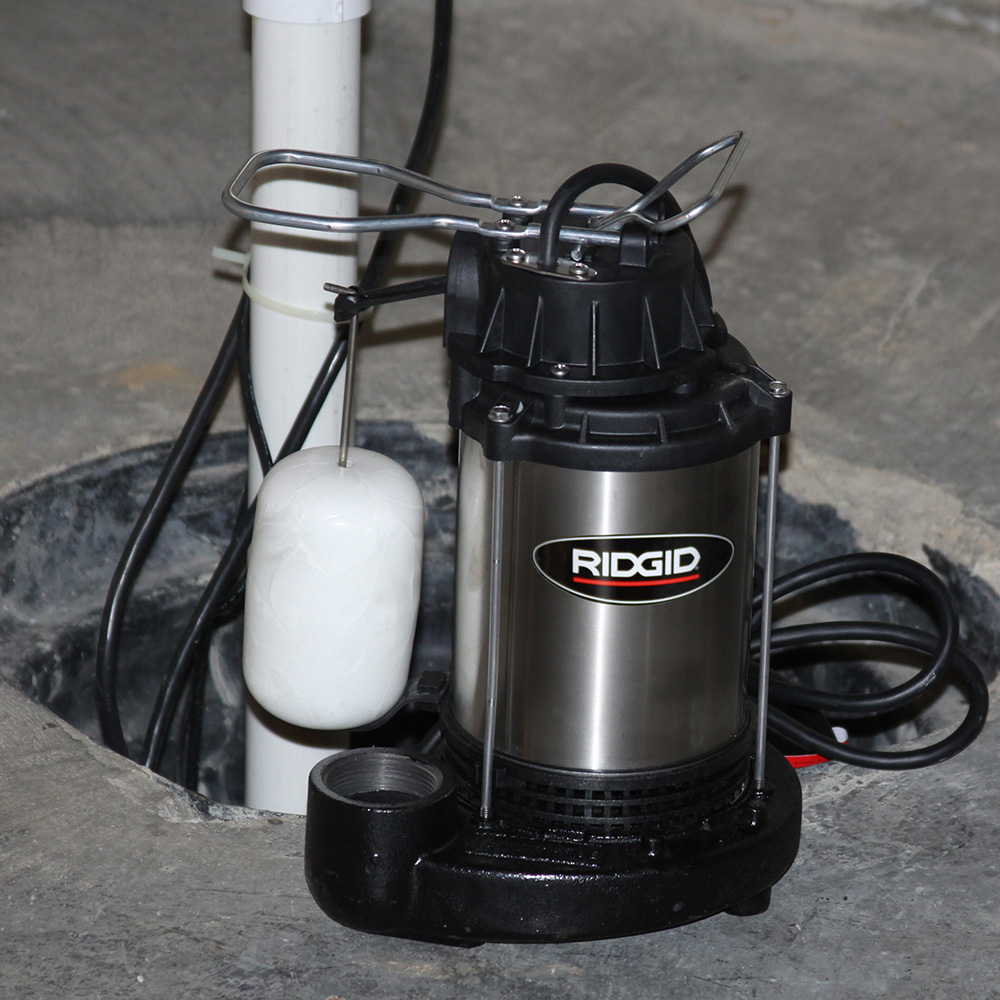 A submersible sump pump sits next to a sump basin.