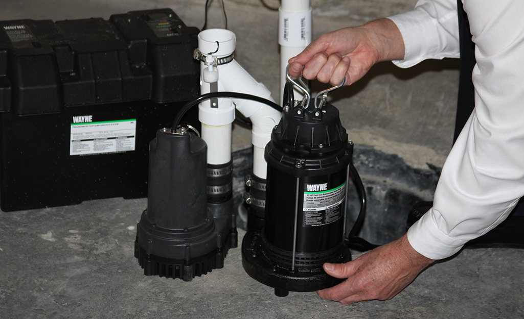 A person preparing to install a submersible sump pump.
