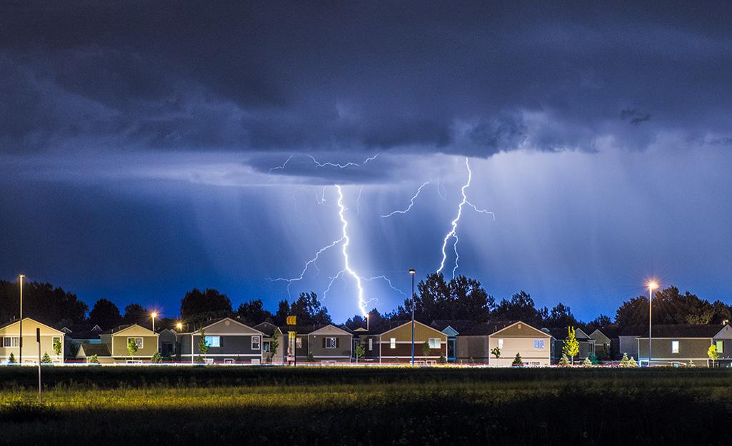 A lightning bolt flashes over a neighborhood/