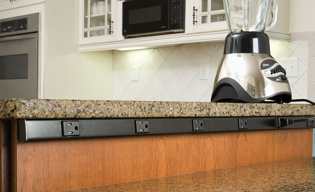 A surge protector power strip mounted underneath a kitchen countertop.