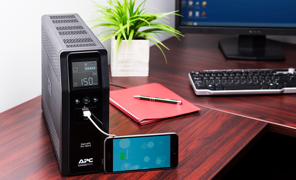 A mobile phone is plugged into a battery backup surge protector on a desk next to a computer.