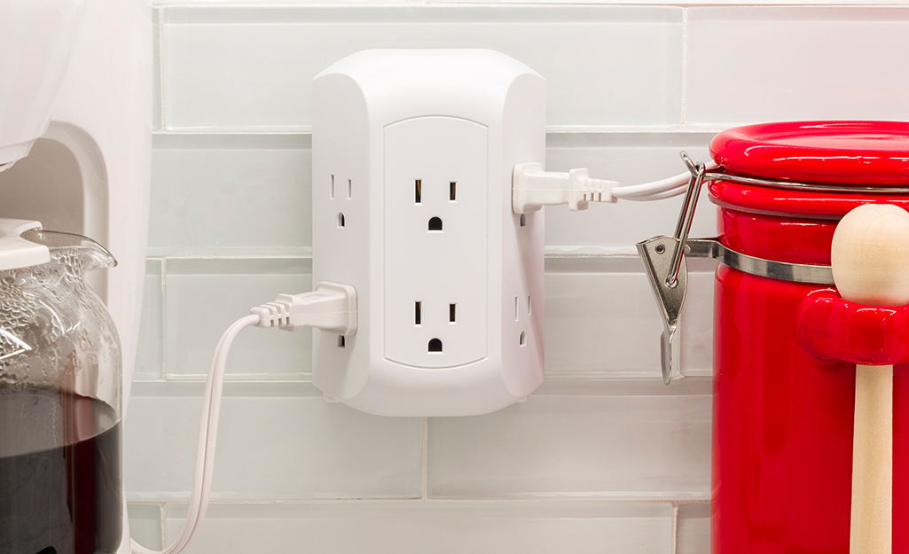 An outlet adapter surge protector installed in a kitchen outlet.