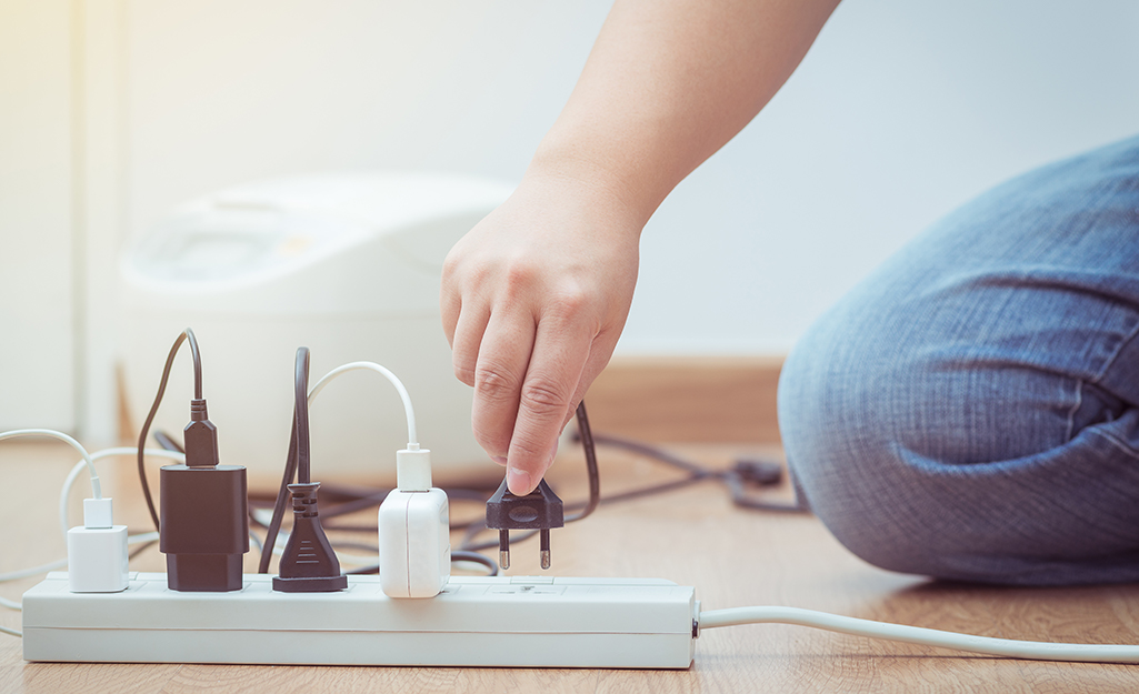 A person plugging a device into a surge protector power strip.