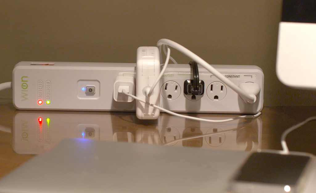 A power strip surge protector placed on a desk.