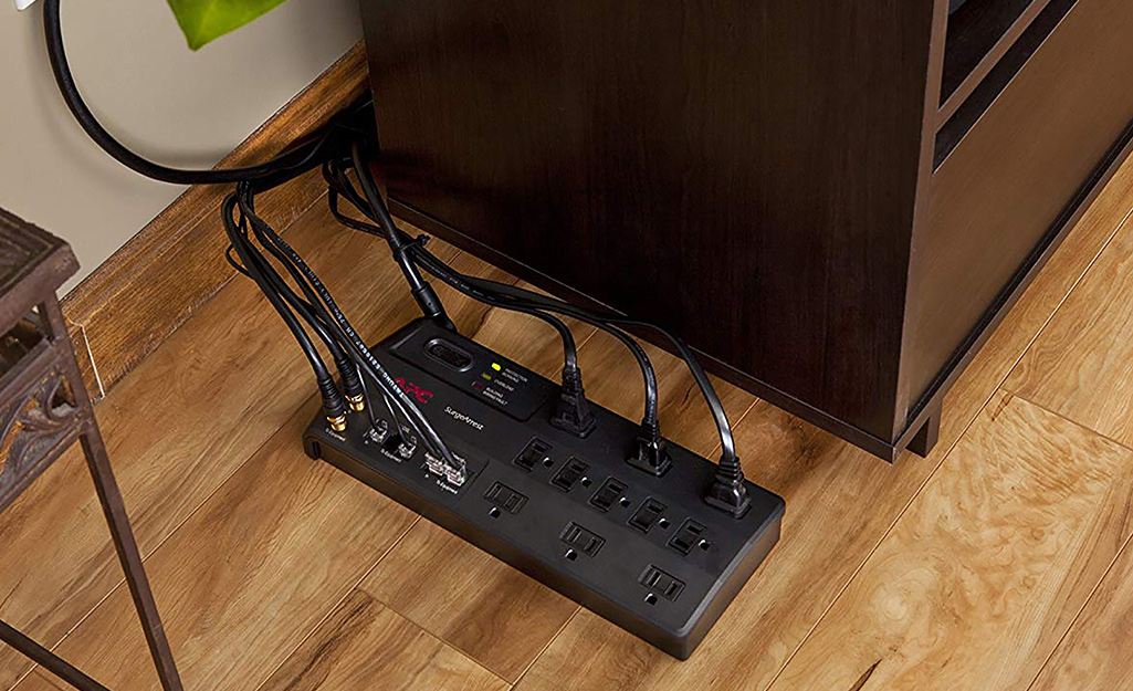 A surge protector with inlets for special components placed next to an entertainment center.