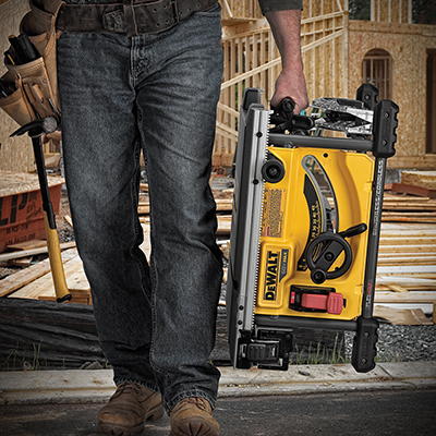 A man carrying a yellow table saw