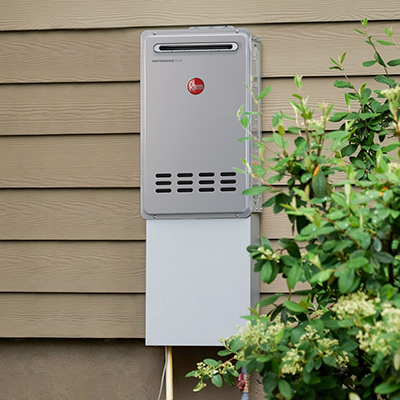 A tankless water heater mounted on the outside of a house.