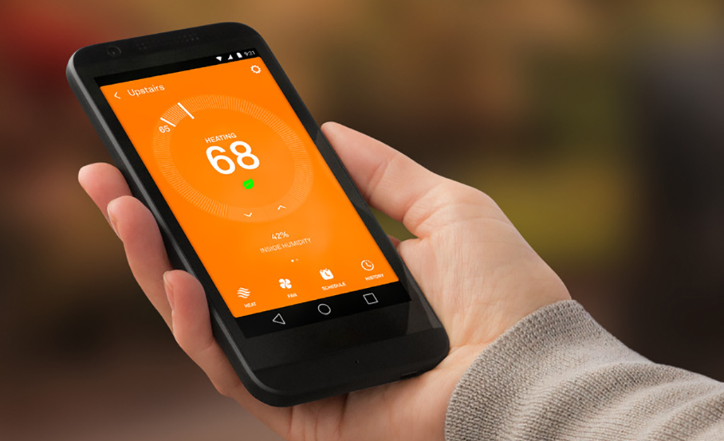 A smartphone showing the interface of an app that controls a smart thermostat.
