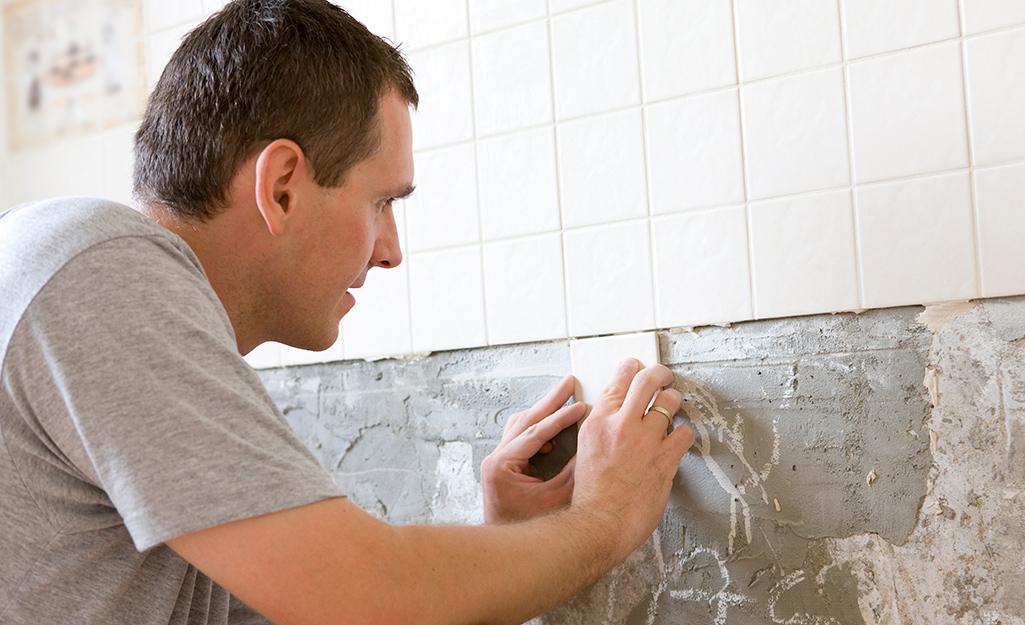 Người đàn ông đang lắp đặt các ô vuông gạch ốp tường màu be.
