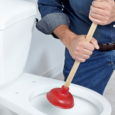 Someone using a plunger to clear a toilet clog.