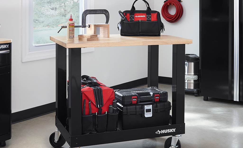A cart displays an assortment of tool belts, bags and pouches.