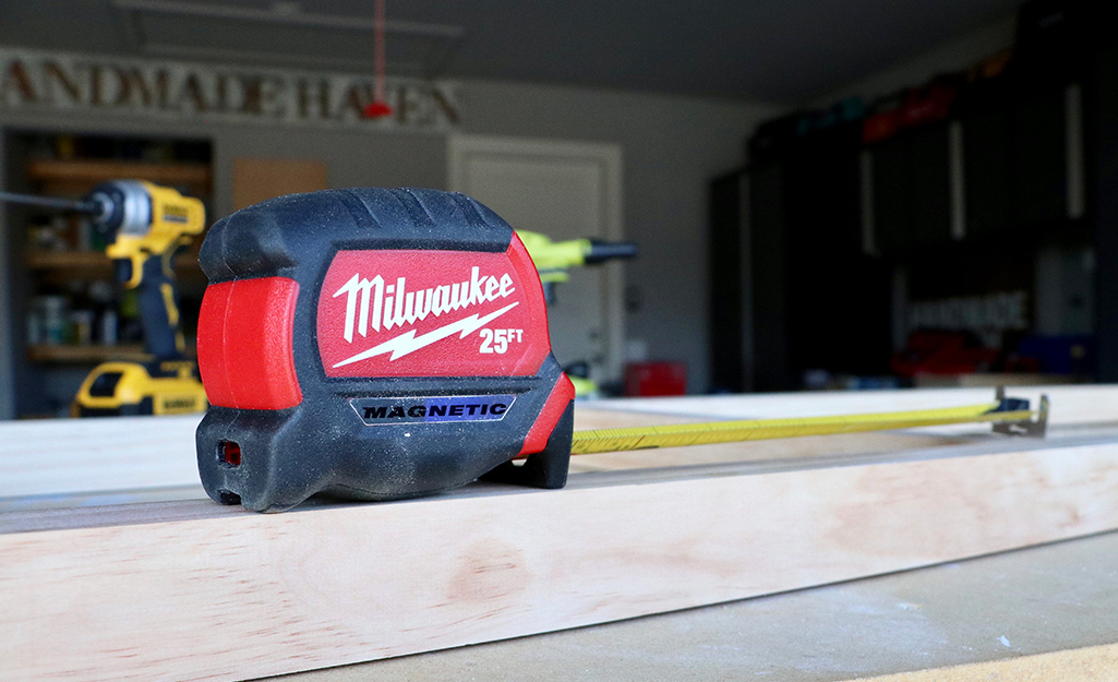 A tape measure sits on a piece of lumber in a garage.