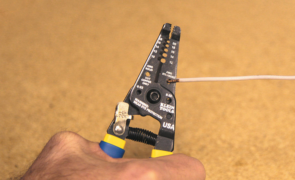 A person uses a pair of wire cutters to cut electrical wire.