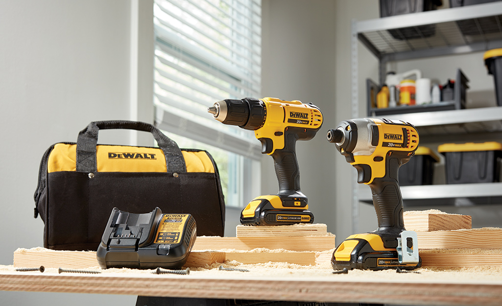 A set of drills sit on a workbench.