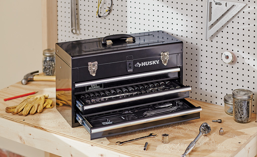 A metal toolbox with drawers open sits on a workbench.