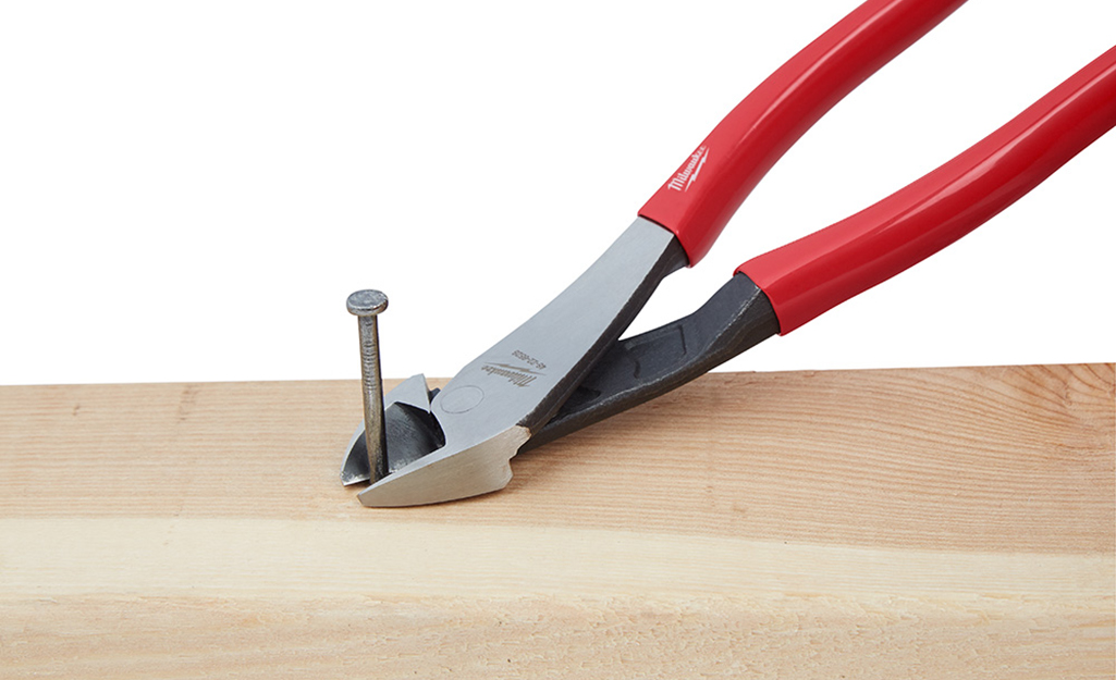 A set of pliers pulls a nail from a piece of wood.