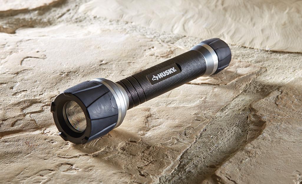 A black flashlight sits on a rock.