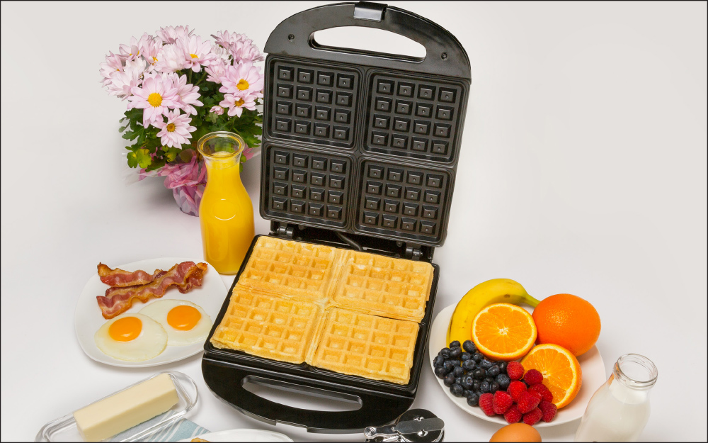a 4-slice waffle maker with a cooked waffle inside, sitting next to a bowl of fresh fruit