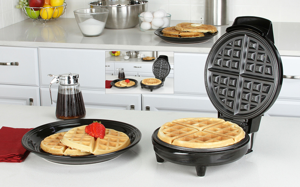 a classic waffle maker with a cooked waffle in it, sitting next to a cooked waffle topped with fruit