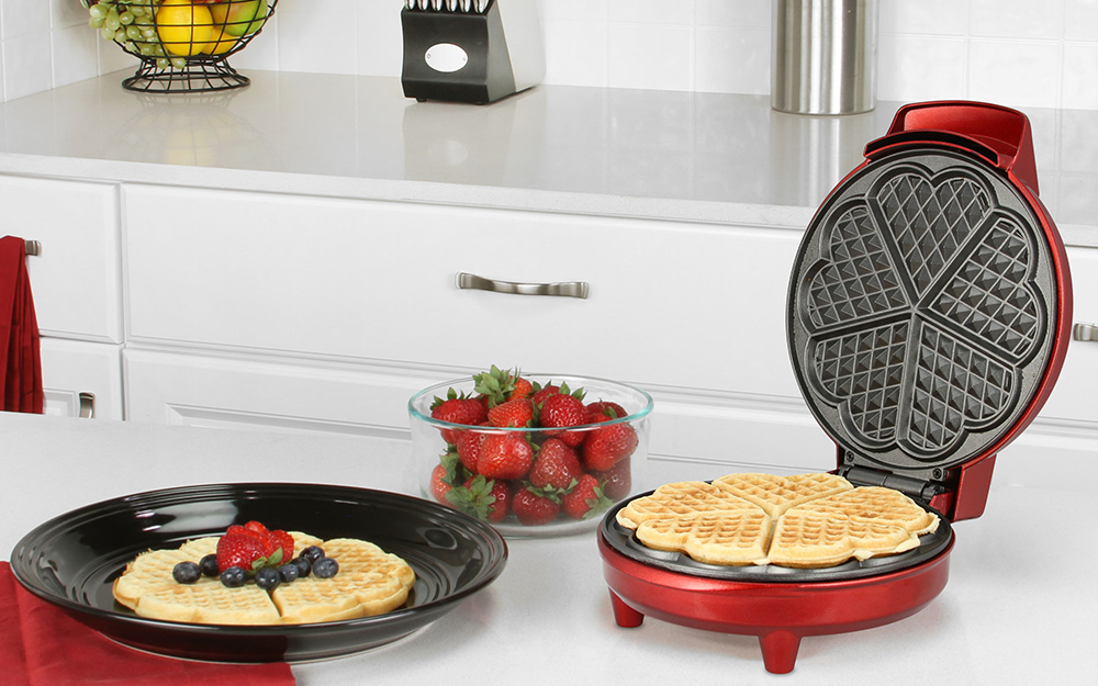 single waffle maker with cooked waffle inside and one waffle sitting off to the side
