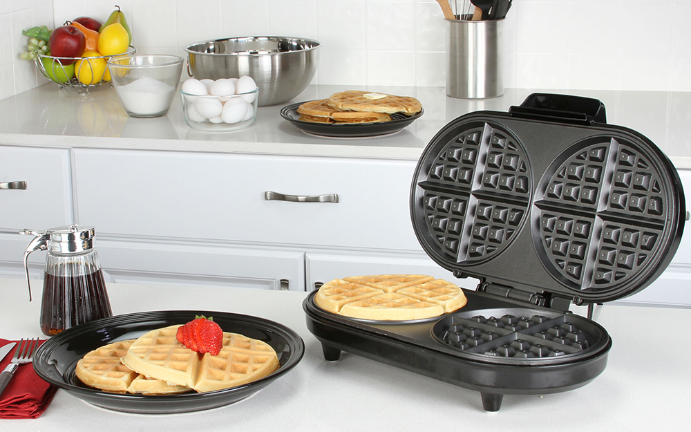double waffle maker with a cooked waffle inside sitting next to a plated waffle