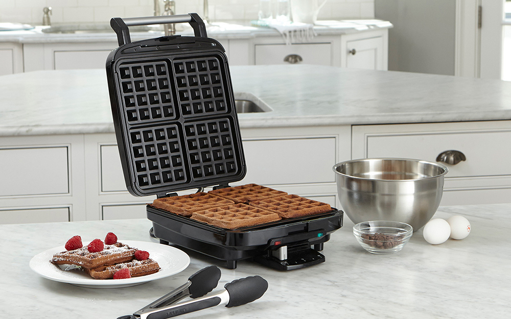 4-slice waffle maker with a cooked waffle inside and one plated off to the side