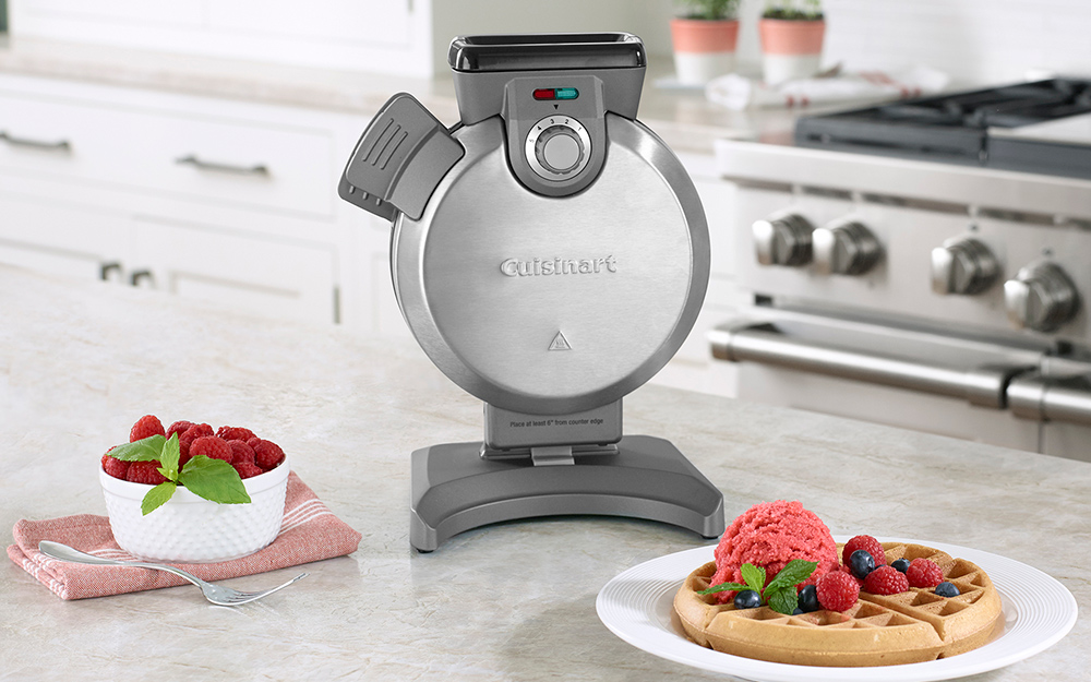vertical waffle maker with a cooked waffle on a plate beside it