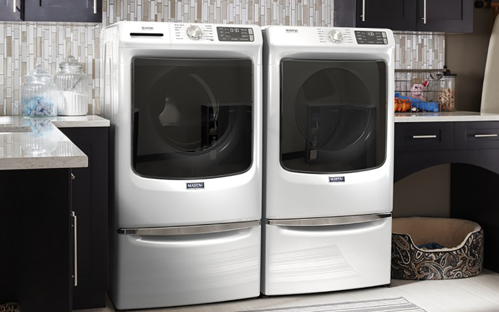 A white front-load washer sitting beside a matching white dryer.