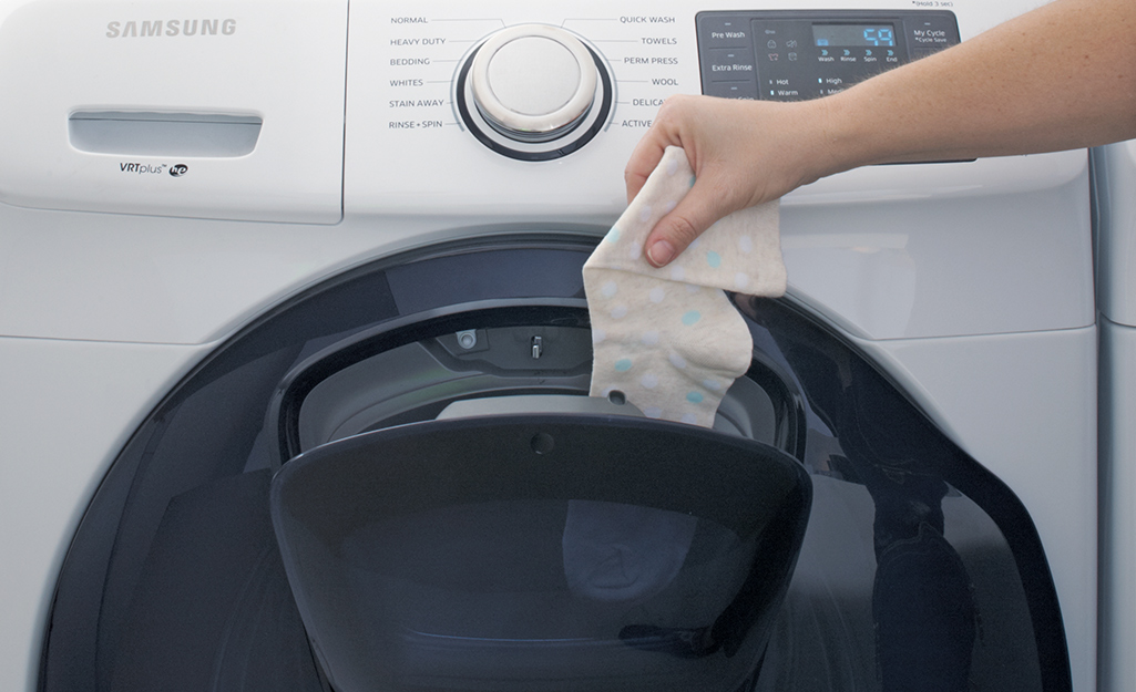 Someone putting a sock in a white, front-load washer with a settings dial and electronic control panel.