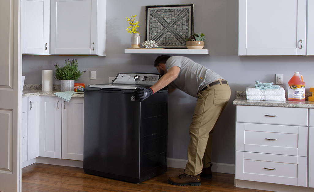 A man installing a black washing machine in a laundry room.