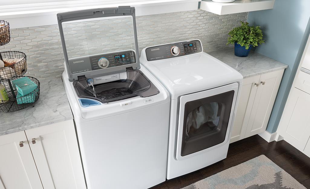 A white top-load high efficiency washer sitting beside a white dryer in a laundry room.