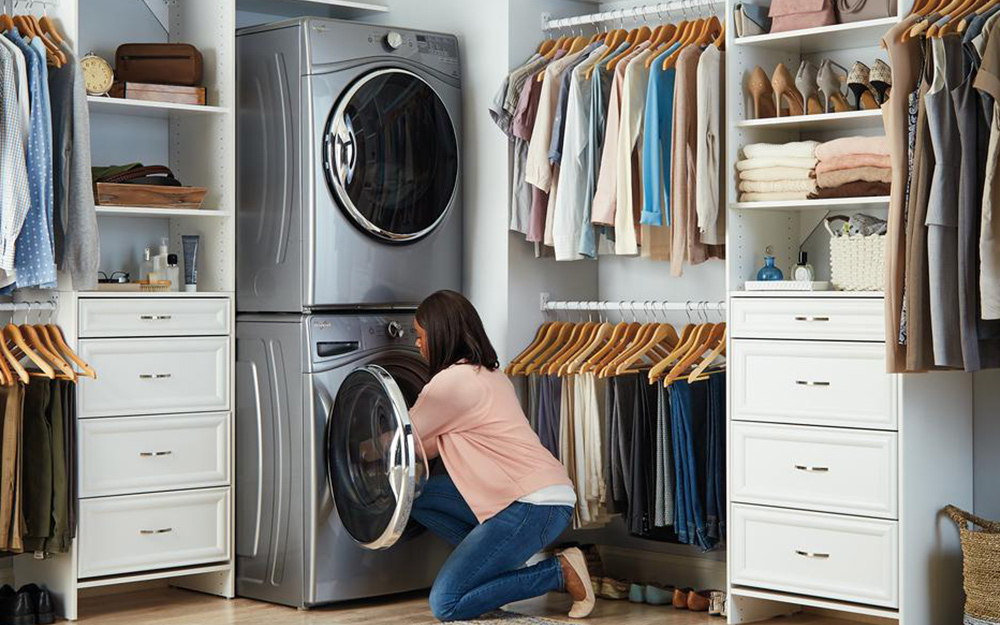 A woman loading a stackable washer in a large clothes closet.